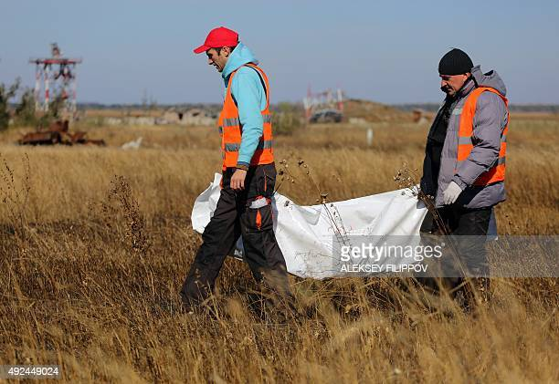Ukrainian volunteers and members of the Red Cross and OSCE collect remains of fallen soldiers in destroyed Donetsk international airport on October...