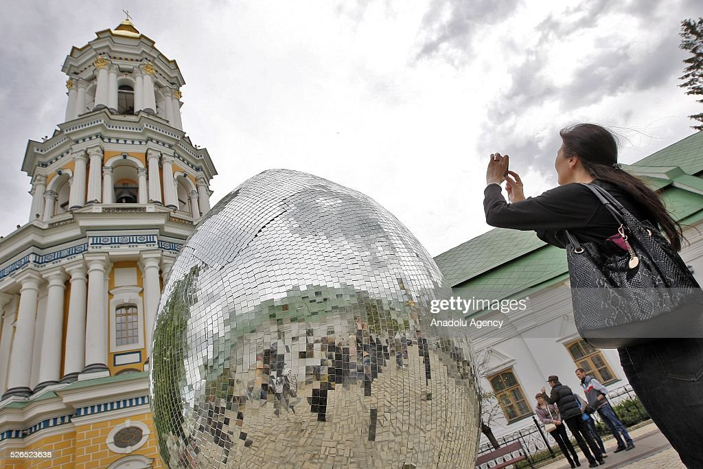 Ukrainian woman photographed a giant egg, named 'Diamond Easter Egg',3.5 m high, which is decorated with more than 15,000 mirror particles during the Ukrainian Easter hand made fair 'Easter country' at the Kiev-Pechersk Lavra in Kiev, Ukraine on April 30, 2016.