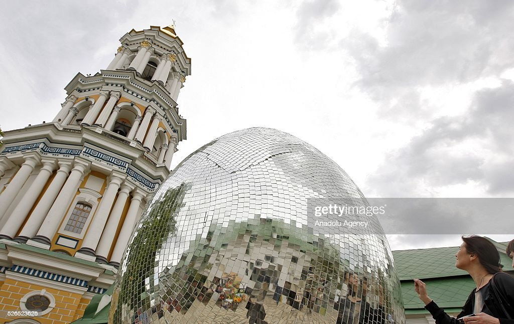 Ukrainian woman stand near a giant egg, named 'Diamond Easter Egg',3.5 m high, which is decorated with more than 15,000 mirror particles during the Ukrainian Easter hand made fair 'Easter country' at the Kiev-Pechersk Lavra in Kiev, Ukraine on April 30, 2016.