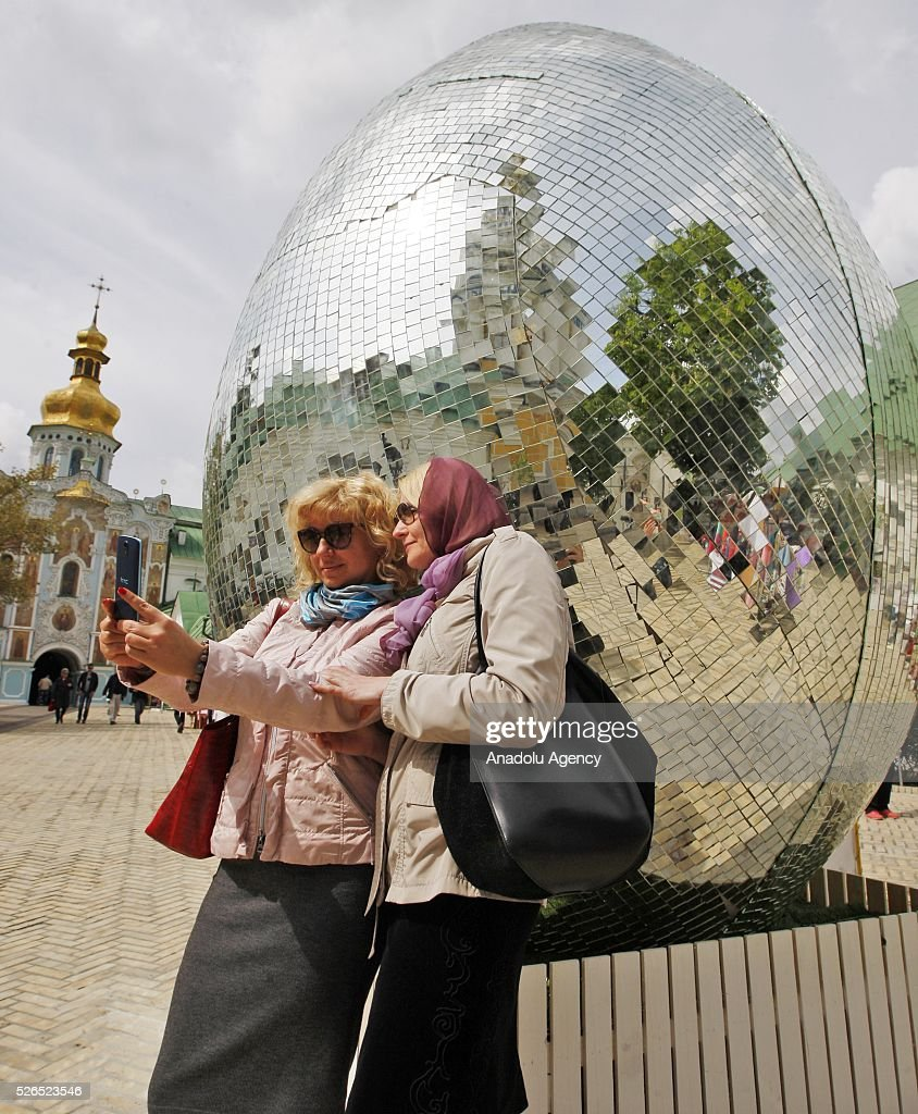 Ukrainian women take a selfie near a giant egg, named 'Diamond Easter Egg',3.5 m high, which is decorated with more than 15,000 mirror particles during the Ukrainian Easter hand made fair 'Easter country' at the Kiev-Pechersk Lavra in Kiev, Ukraine on April 30, 2016.