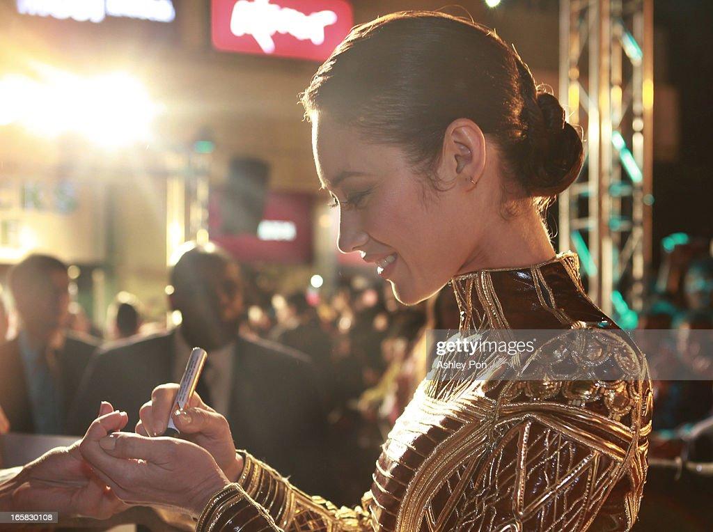 Ukrainian-born actress and model Olga Kurylenko signs her autographs as she arrives at the Taiwan premiere of 'Oblivion' on April 6, 2013 in Taipei, Taiwan.