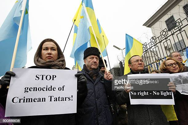 Ukrainians holds a placards reading 'Stop genocide of Crimean Tatars' and 'Crimea No rightsNo light'during a protest of Crimean Tatars and their...