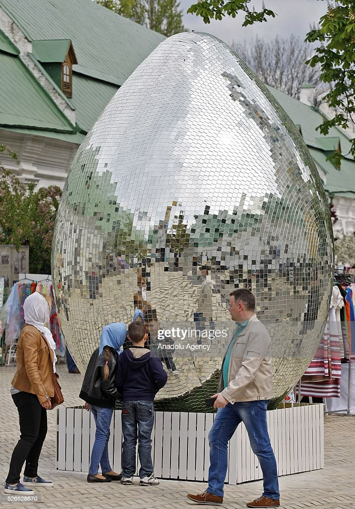 Ukrainians look on a giant egg, named 'Diamond Easter Egg',3.5 m high, which is decorated with more than 15,000 mirror particles during the Ukrainian Easter hand made fair 'Easter country' at the Kiev-Pechersk Lavra in Kiev, Ukraine on April 30, 2016.