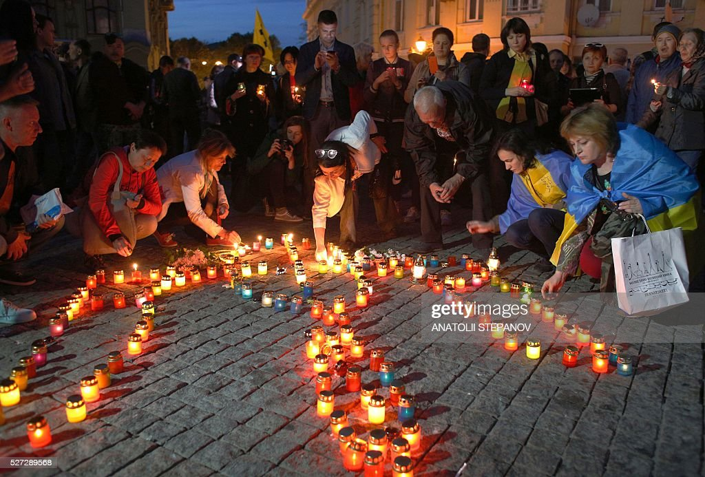 Ukrainians place down lit candles in the shape of the Ukrainian state emblem in Odessa, southern Ukraine, on May 2, 2016, in honour of the pro-Ukrainian activists who were killed during clashes with pro-Russian supporters two years ago. Ukraine's tense Odessa marks two years since street battles between armed backers of the pro-Western government in Kiev and the Kremlin in the historic Black Sea port killed six people and culminated in a building inferno in which 42 pro-Russians died. / AFP / ANATOLII