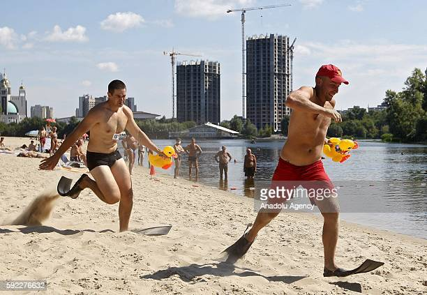 Ukrainians with yellow inflatable ducklings and flippers run along the beach as they take a part in 'Duck Run 2016' in KievUkraineon August 202016...