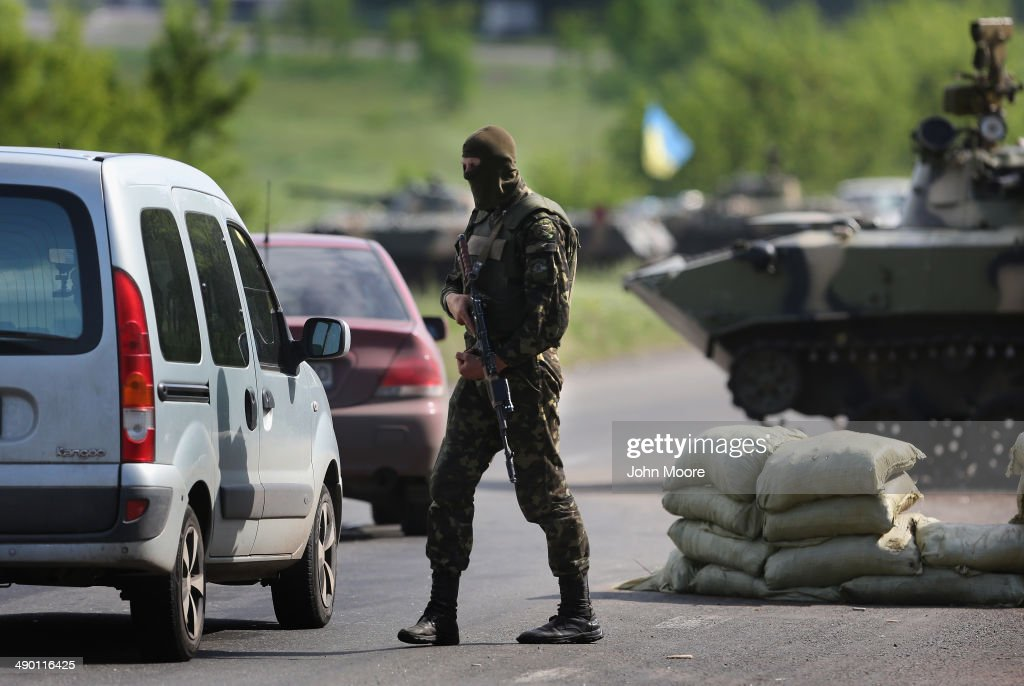Ukranian military soldiers stop cars at a highway checkpoint on May 13, 2014 near Slovansky, Ukraine. At least 6 Ukranian soldiers and more were reportedly injured by pro-Russian separatists in the nearby city of Kramatorsk.