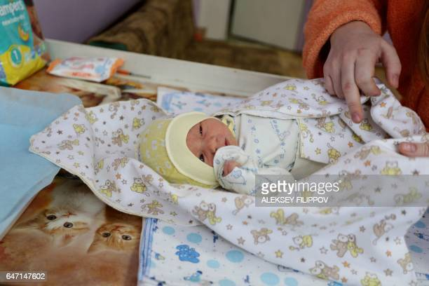 Ukranian woman named only as Olga plays with her newborn baby at the maternity hospital in the eastern Ukrainian city of Avdiivka on January 16 2017...