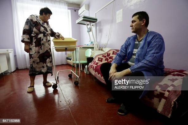 Ukranian woman Olena Gorbatova plays with her baby as her husband Sergiy looks on at the maternity hospital in the eastern Ukrainian city of Avdiivka...