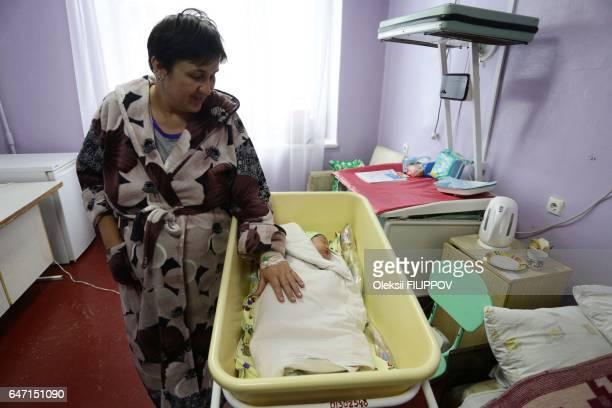 Ukranian woman Olena Gorbatova plays with her baby at the maternity hospital in the eastern Ukrainian city of Avdiivka on January 16 2017 Olena...