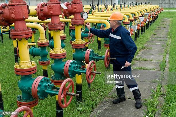 A UkrTransGaz employee adjusts a pressure gauge on pipework at the Dashava underground gas storage facility operated by UkrTransGaz a unit of NAK...