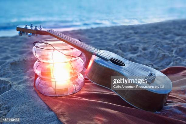 Ukulele resting on lantern on beach