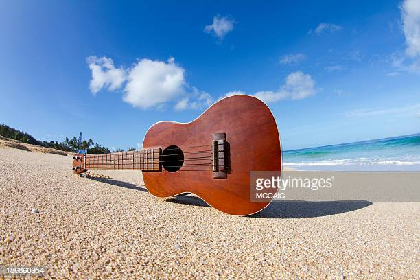 A ukulele sitting on its side on a Hawaiian beach