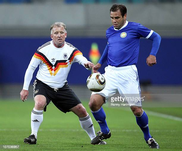 Ulf Kirsten of the DFV Legend battles for the ball with Andreas Brehme of the World Champion 1990 during the Reunification match between the World...