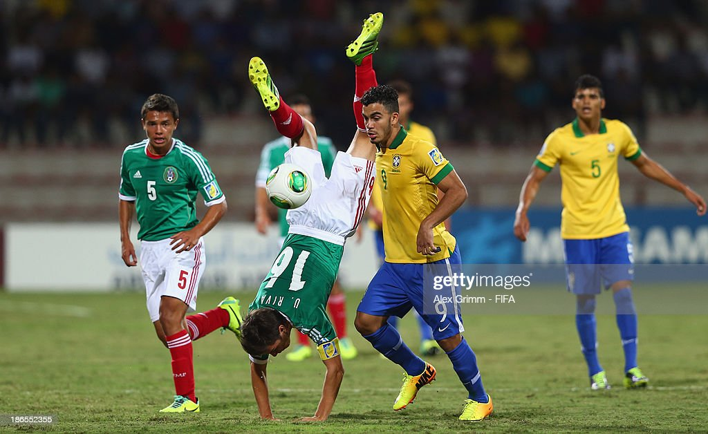 Ulises Rivas (2L) of Mexico is challenged by Mosquito of Brazil during the FIFA U-17 World Cup UAE 2013 Quarter Final match between Brazil and Mexico at Al Rashid Stadium on November 1, 2013 in Dubai, United Arab Emirates.