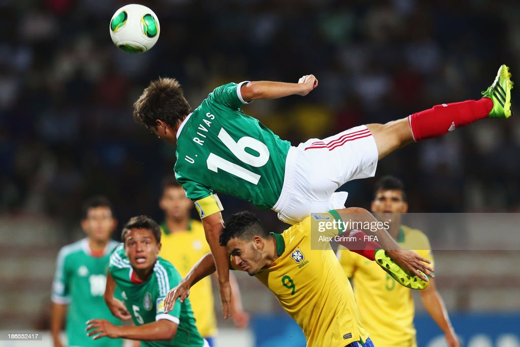 Ulises Rivas (top) of Mexico is challenged by Mosquito of Brazil during the FIFA U-17 World Cup UAE 2013 Quarter Final match between Brazil and Mexico at Al Rashid Stadium on November 1, 2013 in Dubai, United Arab Emirates.