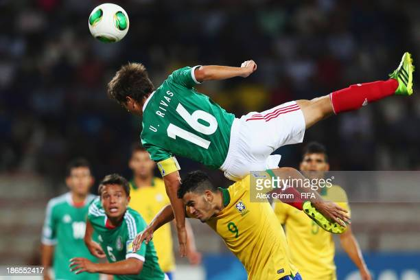 Ulises Rivas of Mexico is challenged by Mosquito of Brazil during the FIFA U17 World Cup UAE 2013 Quarter Final match between Brazil and Mexico at Al...