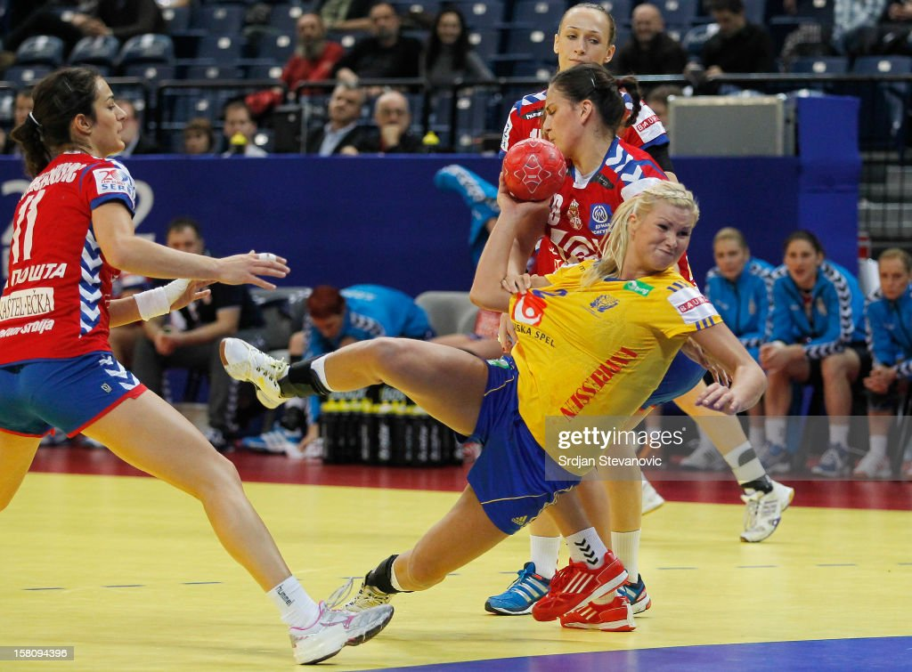 Ulrika Agren (C) of Sweden is challenged by Sladjana Pop-Lazic (R) of Serbia during the Women's European Handball Championship 2012 Group I main round match between Serbia and Sweden at Arena Hall on December 10, 2012 in Belgrade, Serbia.