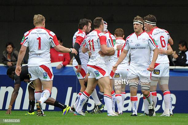 Ulster Andrew Trimble is congratulated by teammates after scoring a try on October 19 2013 during a European Cup rugby union match at the Yves du...