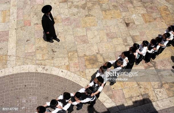 Ultra Orthodox children line up outside their kindergarten at Mea Shearim neighborhood in Jerusalem 31 May 2006 during celebration of the Jewish...