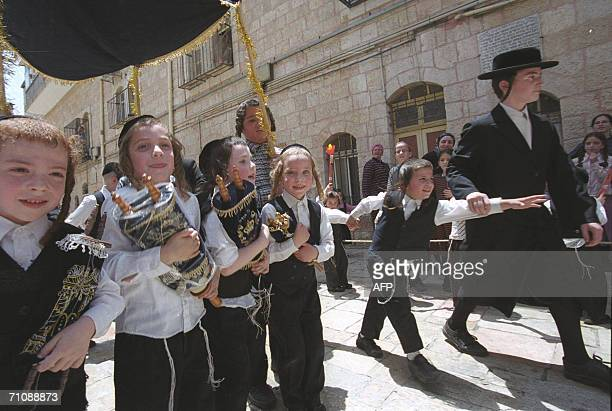 Ultra Orthodox children march with Torah scrolls at Mea Shearim neighborhood in Jerusalem 31 May 2006 during celebration of the Jewish holiday of...