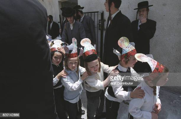 Ultra Orthodox children wear Torah crowns during a march at their Mea Shearim neighborhood in Jerusalem 31 May 2006 during celebration of the Jewish...