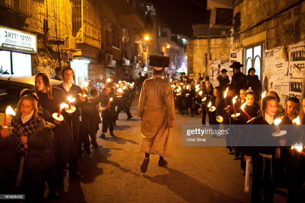 Ultra Orthodox Jewish children of the Ultra-Orthodox Tholdot Avraham Yizhak Hasidic dynasty march with torches during an inauguration ceremony for the holy book in an Ultra Orthodox neighborhood of Mea Shearim on February 17, 2013 in Jerusalem, Israel. The Torah is also known as the first five books of Moses. Hundreds of Ultra Orthodox Jews marched and danced with the Torah through the neighbourhood into the synagogue where they place the Torah.