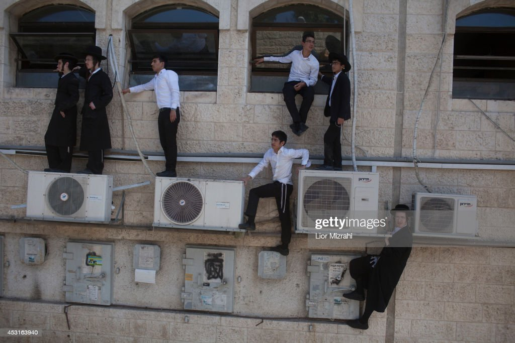 Ultra Orthodox Jewish men gather near where a Palestinian man rammed an excavator into a bus on August 04, 2014 in Jerusalem, Israel. The man driving the excavator used the machinery to flip over a bus, killing one. In a seperate incedent, a gunman on a motorcycle opened fire August 4, on a hitchhiking station near Jerusalem's Hebrew University on Mt. Scopus. Several people were wounded in both attacks.