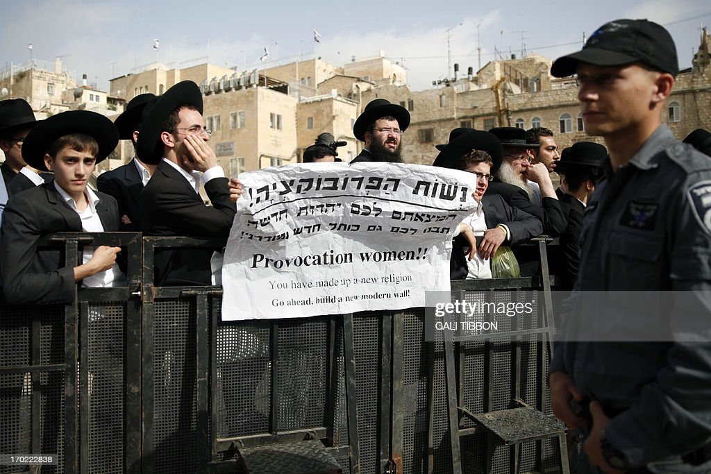 Ultra Orthodox Jewish men hold a banner to protest against members of the liberal Jewish religious group Women of the Wall who pray with traditional Jewish prayer apparel for men on June 9, 2013 at the Western Wall in Jerusalem's Old City marking the first day of the Jew sh month of Tamuz.