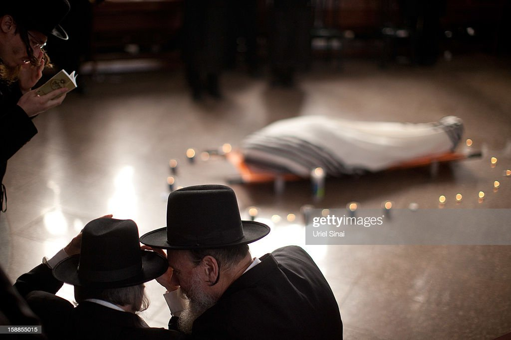 Ultra Orthodox Jewish men pray next to the body of Rabbi Abraham Jacob Friedman of Sadigura Hasidic dynasty during his funeral on January 01, 2013. in Bnei Brak, Israel. The Rabbi was the leader of the Sadigura Hasidic dynasty in Bnei Brak and died at the age of 84.