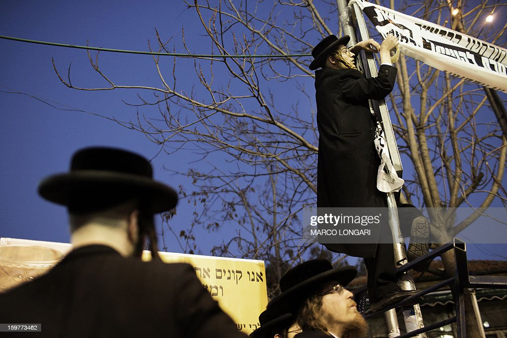 Ultra Orthodox Jews belonging to the Satmar Hasidic group headed by Satmar Rebbe of Williamsburg, Rabbi Zalman Leib Teitelbaum, hang banners reading in Hebrew 'our holy Torah forbids participation in the profane elections' during a anti-election rally in the conservative Mea Shearim neighbourhood of Jerusalem on January 20, 2013, two days before nationwide voting for the general election gets underway on January 22. AFP PHOTO/MARCO LONGARI