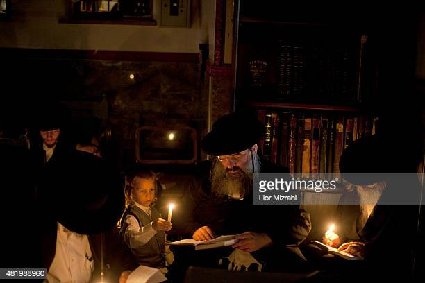 Ultra Orthodox Jews light candles and pray on the floor as they read from the book of Eicha as they mark Tisha Be'ave at a synagogue in the Mea...