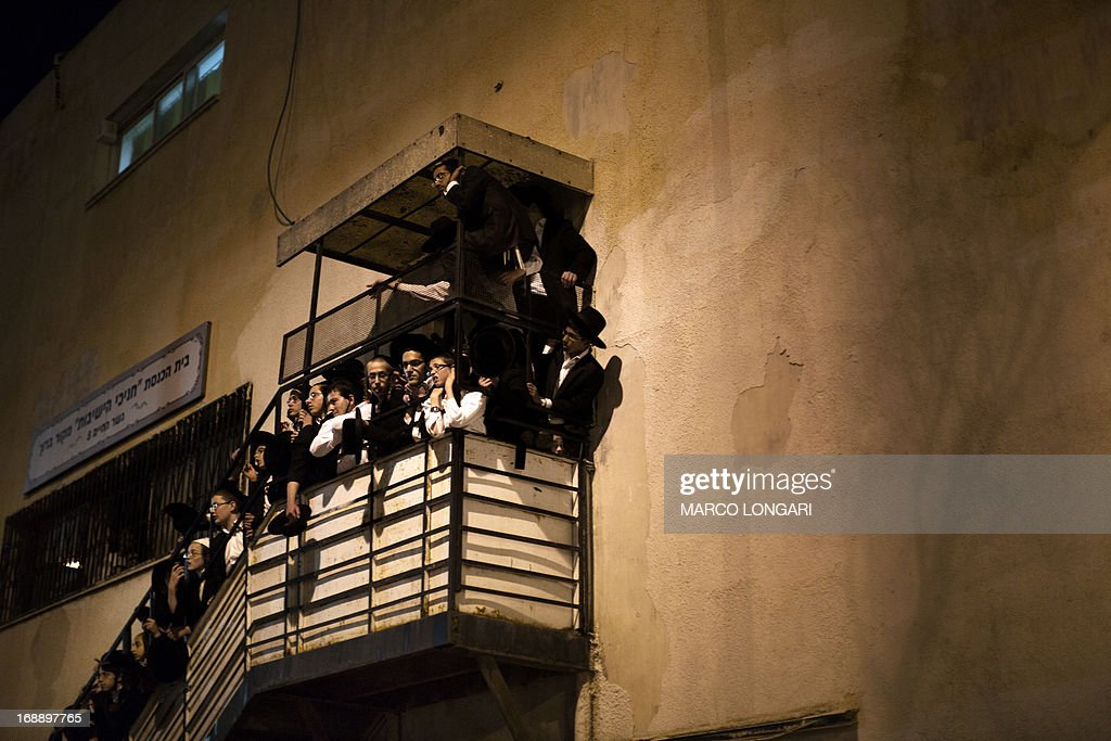 Ultra Orthodox Jews observe from a stair while thousands Orthodox Jew gather in front of the main army recruitment office in Jerusalem on May 16, 2013 to demonstrate against any plans to make them undergo military service, a police spokesman said. Protesters also prayed and chanted 'the Torah above everything!' referring to Jewish religious law, and 'the army will not take yeshiva (religious seminary) pupils.'
