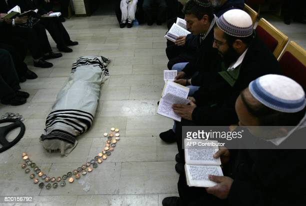 Ultra Orthodox Jews pray before the start of the funeral of Rabbi Yitzhak Kaduri wrapped in the Talit or religious shawl and surrounded by candles 29...