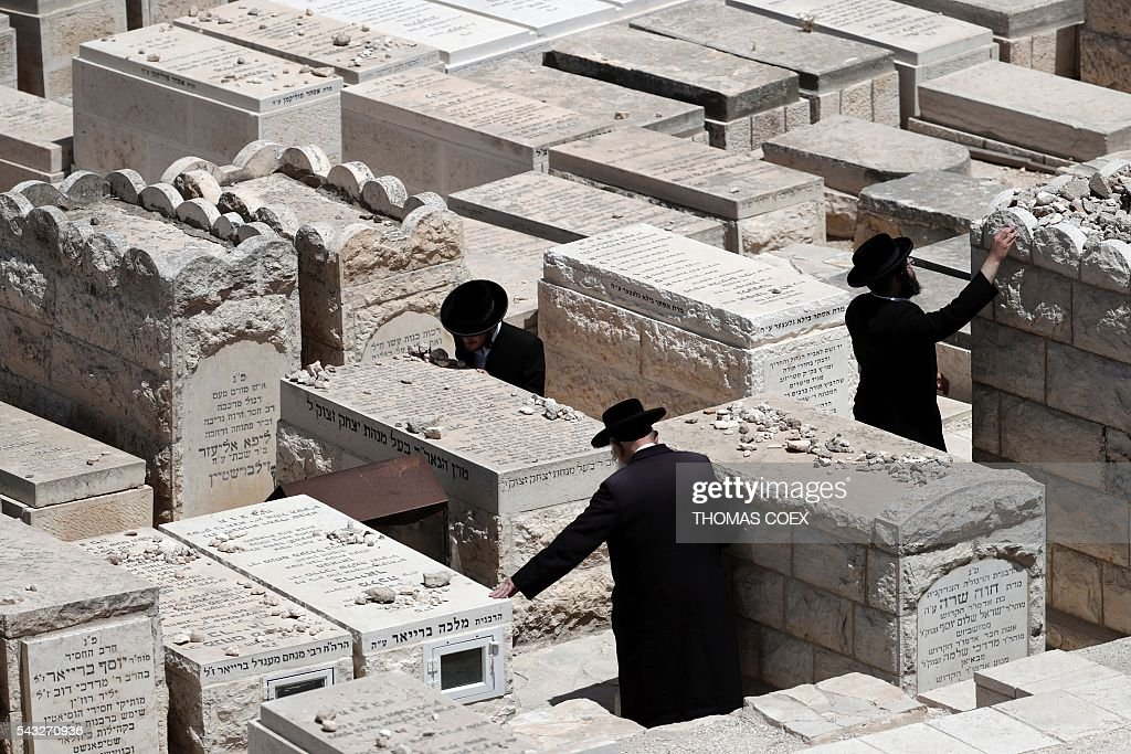 Ultra Orthodox Jews pray over a tomb inside the cemetery of the Mount of Olives in east Jerusalem on June 27, 2016. / AFP / THOMAS