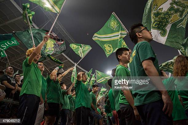 Ultra supporters and fans of the Beijing Guoan FC cheer together during their match against Chongcing Lifan FC in Chinese Super League play on June...