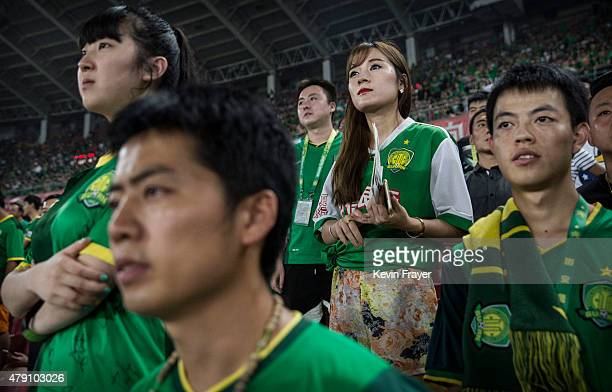 Ultra supporters and fans of the Beijing Guoan FC watch their team play against Chongcing Lifan FC during their Chinese Super League match on June 28...