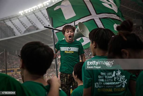 Ultra supporters of the Beijing Guoan FC chant slogans during their Chinese Super League match against Chongcing Lifan FC on June 28 2015 in Beijing...