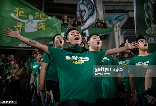 Ultra supporters of the Beijing Guoan FC chant slogans during their Chinese Super League match against Tianjin FC on June 20 2015 in Beijing China...