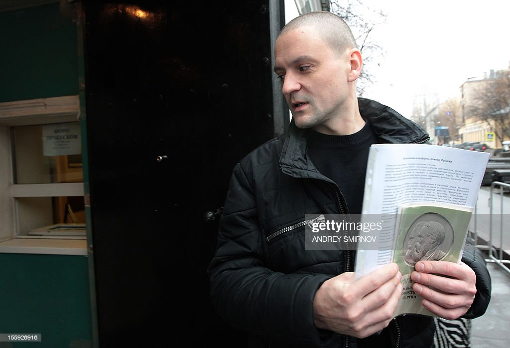 Ultra-left opposition leader Sergei Udaltsov holds a copy of The Communist Manifesto by Karl Marx and Friedrich Engels as he speaks to media after arriving for questioning at Moscow's Prosecutors Office, on November 9, 2012. Russian Investigative Committee in recent days has charged Udaltsov with preparing mass riots. AFP PHOTO / ANDREY SMIRNOV