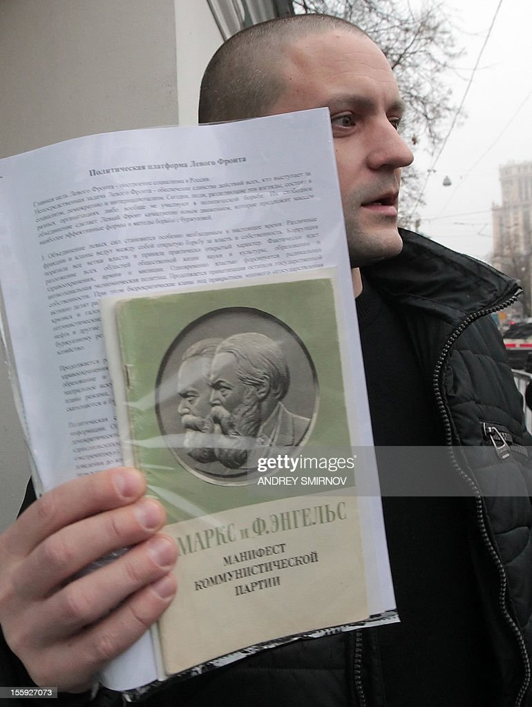Ultra-left opposition leader Sergei Udaltsov holds a copy of The Communist Manifesto by Karl Marx and Friedrich Engels as he speaks to media after arriving for questioning at Moscow's Prosecutors Office, on November 9, 2012. Russian Investigative Committee in recent days has charged Udaltsov with preparing mass riots.