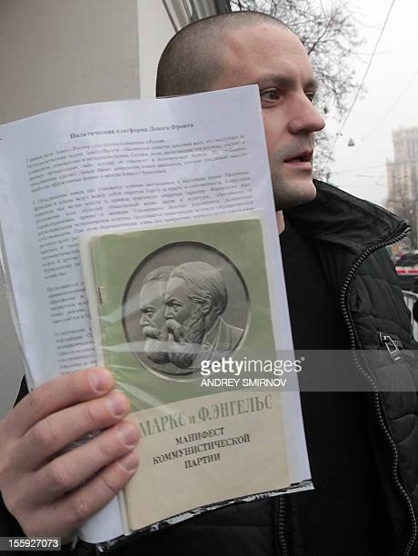 Ultraleft opposition leader Sergei Udaltsov holds a copy of The Communist Manifesto by Karl Marx and Friedrich Engels as he speaks to media after...