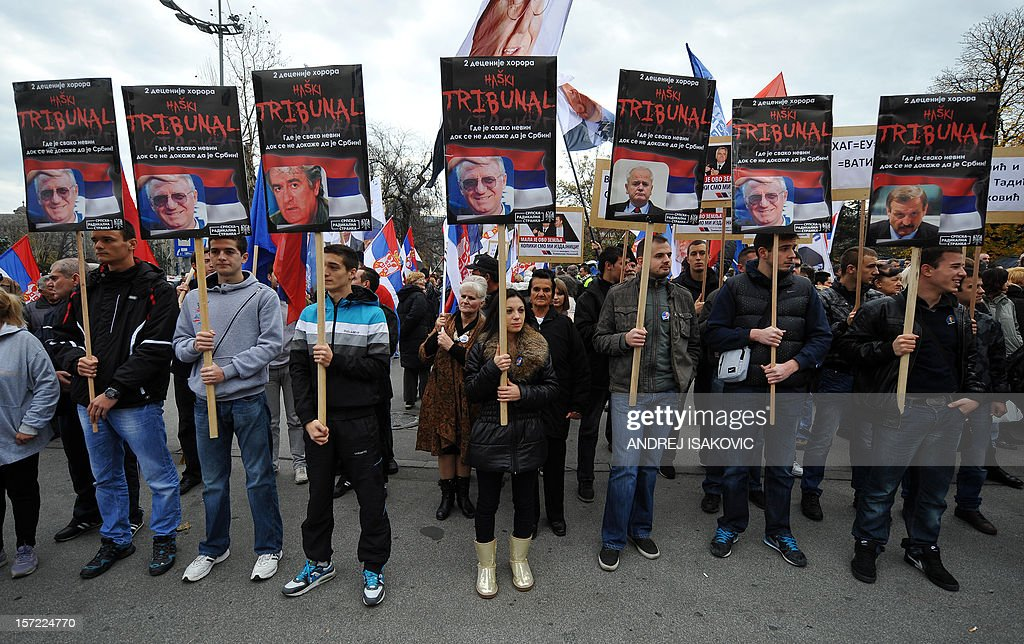 Ultra-nationalist Serbs hold posters of Serbian Radical Party (SRS) leader Vojislav Seselj (C), Bosnian Serb wartime leader Radovan Karadzic (3rdL) and late Yugoslav president Slobodan Milosevic on November 30, 2012 during a protest held in front of the Serbian Presidency in downtown Belgrade against the International Criminal Tribunal for the Former Yugoslavia (ICTY) court after it cleared ethnic Albanian former rebel chief Ramush Haradinaj of war crimes. Hundreds of demonstrators asked the authorities to give up their bid to become a member of the European Union. AFP PHOTO / ANDREJ ISAKOVIC