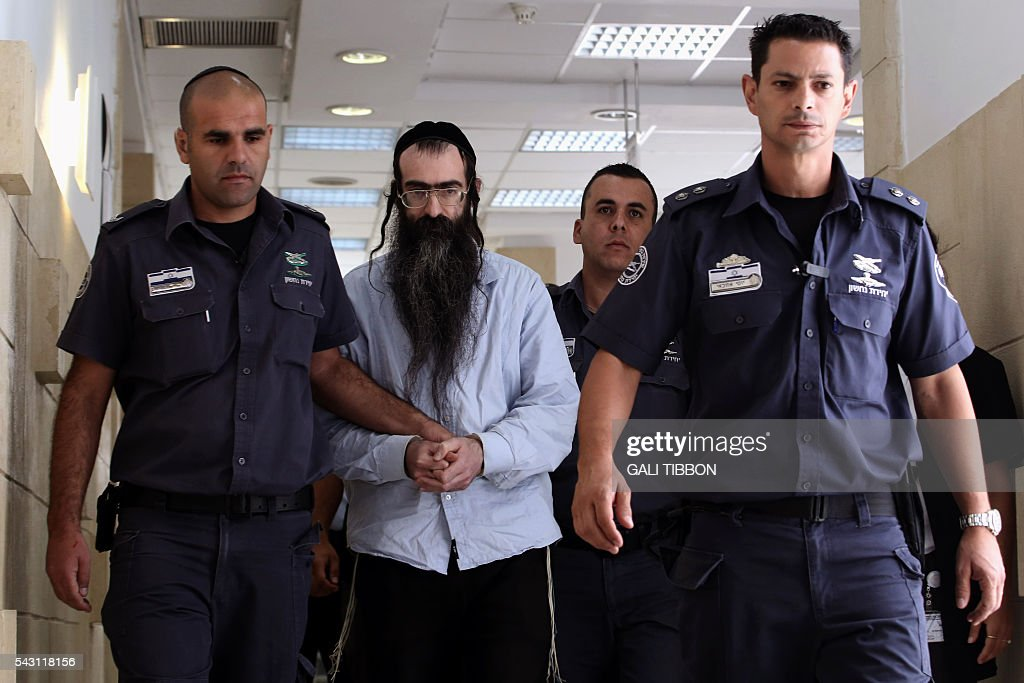 Ultra-Orthodox Jew Yishai Shlissel (C), who was convicted of killing a 16-year-old Israeli girl during the Jerusalem Gay Pride parade last year, is escorted by policemen into the courtroom, on June 26, 2016 at the Jerusalem district court. The Jerusalem District Court convicted Schlissel in April of murder and six counts of attempted murder over the July 2015 stabbings. He was sentenced to life plus 31 years, a court statement said, after prosecutors had requested life plus 60 years. / AFP / GALI