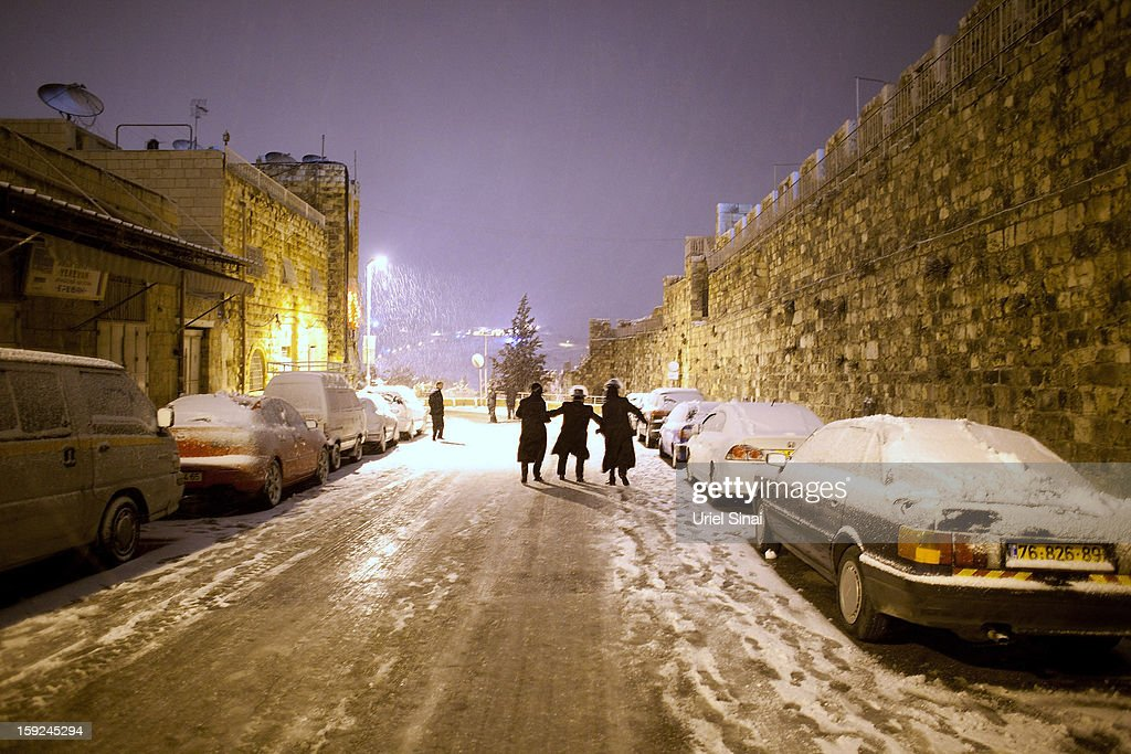 Ultra-Orthodox Jewish boys walk down a snow-covered street on January 9, 2013 in Jerusalem, Israel. Snow and strong winds have affected regions across the Middle East.