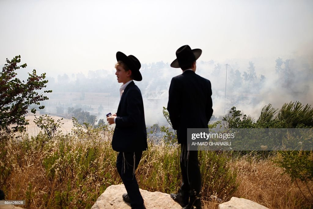 Ultra-Orthodox Jewish boys watch as firefighters work to put out a fire that is spreading in the woods around Jerusalem on May 26, 2016 / AFP / AHMAD