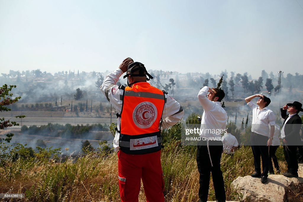 Ultra-Orthodox Jewish children and a member of the Red Crescent watch as firefighters work to put out a fire that is spreading in the woods around Jerusalem on May 26, 2016 / AFP / AHMAD