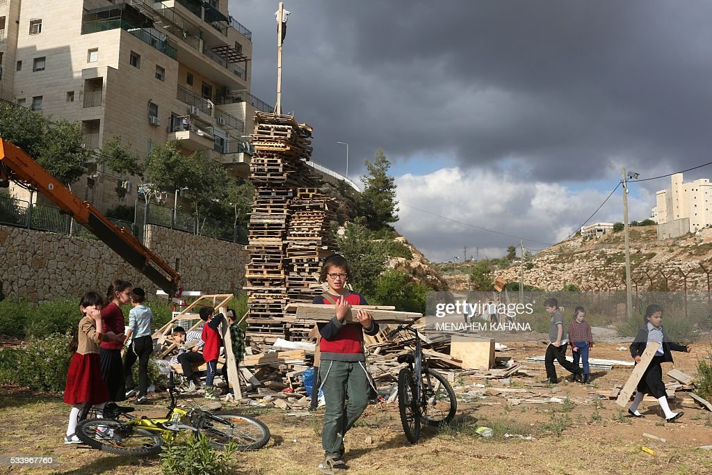 Ultra-Orthodox Jewish children build a bonfire in the West Bank settlement of Beitar Illit on May 24, 2016 one day ahead celebrations of Lag BaOmer . The Lag BaOmer bonfire is lit to commemorate the death of renowned Jewish scholar and renowned Bar Yochai some 1800 years ago. In a night long vigil thousands of Jews will light large bonfires and visit the final resting place of Bar Yochai, who is revered as one of Judaism's great sages. / AFP / MENAHEM