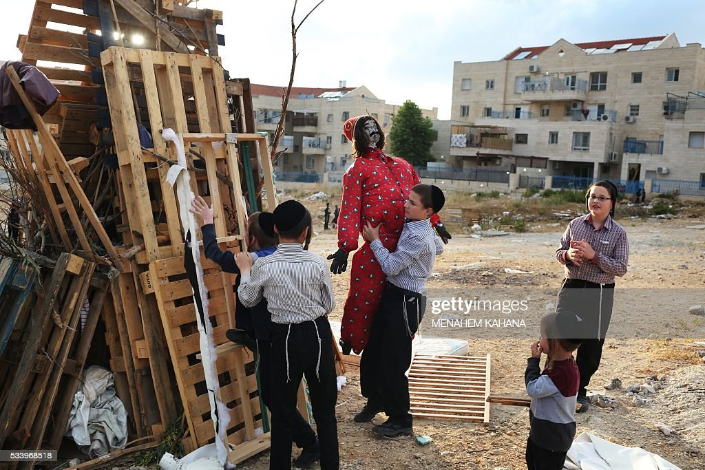 Ultra-Orthodox Jewish children build a bonfire where an effigy of the 'evil man' will be burnt in the West Bank Settlement of Beitar Illit on May 24, 2016 one day ahead celebrations of Lag BaOmer The Lag BaOmer bonfire is lit to commemorate the death of renowned Jewish scholar and renowned Bar Yochai some 1800 years ago. In a night long vigil thousands of Jews will light large bonfires and visit the final resting place of Bar Yochai, who is revered as one of Judaism's great sages. / AFP / MENAHEM