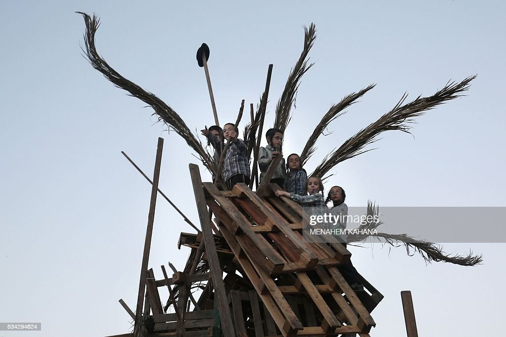 Ultra-Orthodox Jewish children prepare a giant bonfire before lighting it in the Mea Shearim neighborhood of Jerusalem on May 25,2016 during the celebration of Lag BaOmer. The Lag BaOmer bonfire is lit to commemorate the death of renowned Jewish scholar and renowned Bar Yochai some 1800 years ago. In a night long vigil thousands of Jews will light large bonfires and visit the final resting place of Bar Yochai, who is revered as one of Judaism's great sages. / AFP / MENAHEM