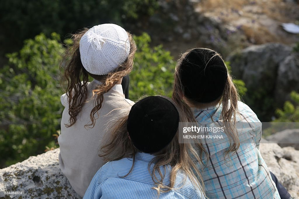 Ultra-Orthodox Jewish children stand at the grave site of Rabbi Shimon Bar Yochai in the northern Israeli village of Meron, on May 26 2016, at the start of the day-long holiday of Lag Baomer that commemorates the Jewish scholar's death. Thousands of religious Jews light large bonfires all night long and visit the shrine of Bar Yochai, one of the most prominent sages in Jewish history, during the holiday. KAHANA